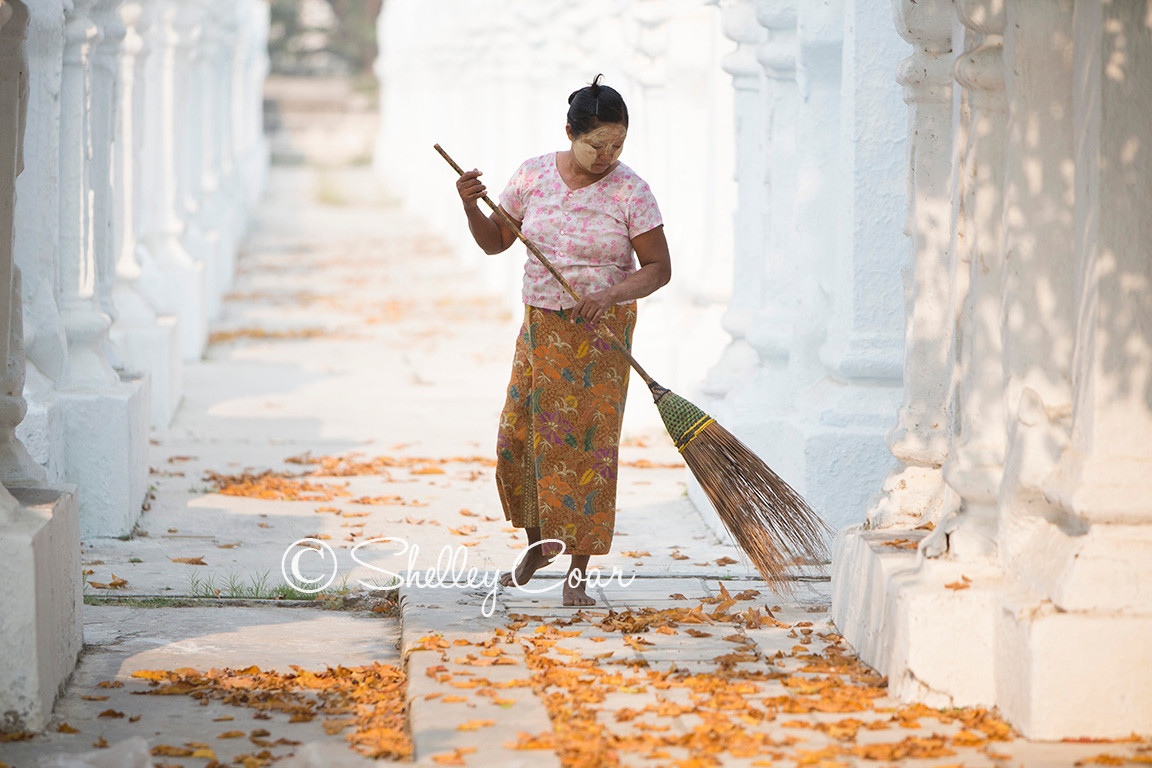 A photograph of a woman sweeping up leaves in the early morning at Kuthodaw Pagoda in Mandalay, Myanmar by Shelley Coar.