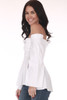 Side shows off shoulder white button up blouse with long wide flared sleeves and smock top.
