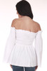 Back shows white off shoulder blouse with long wide sleeves and smock top.