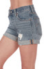 Side shows cuffed long 501 denim shorts with rip on left side and pockets.