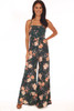 Front shows dark emerald green jumpsuit all over floral print with adjustable criss-cross  spaghetti straps, middle back tie, hidden zipper at middle back and wide flare  bottoms.