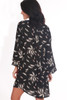 Back shows black long sleeve mini dress featuring an all over feather print with long bell sleeves and sheer material.