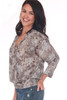 side shows brown and grey patterned blouse featuring a surplice front with 3/4 length sleeves, dolman fit and elastic band at bottom. Worn with blue jeans.