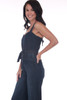 side shows blue denim jumpsuit featuring culotte length pants with thin adjustable tying straps, sash at waist and hidden side zipper.