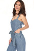 Side view shows front pockets and side zipper of this Denim jumpsuit with tie waist which fits True To Size.  This jumpsuit has wide spaghetti straps and has a Side Zipper Closure with wide cropped pant. Shoulder To Hem Measurement is  Approximately 52.5 inches.  100% Cotton.  Machine Wash Cold, Hang Dry