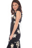 Side view of this long sleeveless dress which is black with a white flower pattern shows ruffle at shoulder and bare arm.  Side Zipper Opening.  Hook & Eye at front V.  Slit on front to just above one.  Shoulder To Hem Measurement is approximately 53 inches at longest point. 100% Rayon.  Machine Wash Cold, Hang Dry.