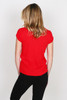 back shows bright red worn-in tee featuring knotted detailing on the cuffs. This easy tee has unfinished trim throughout. Shown worn with  black pants.