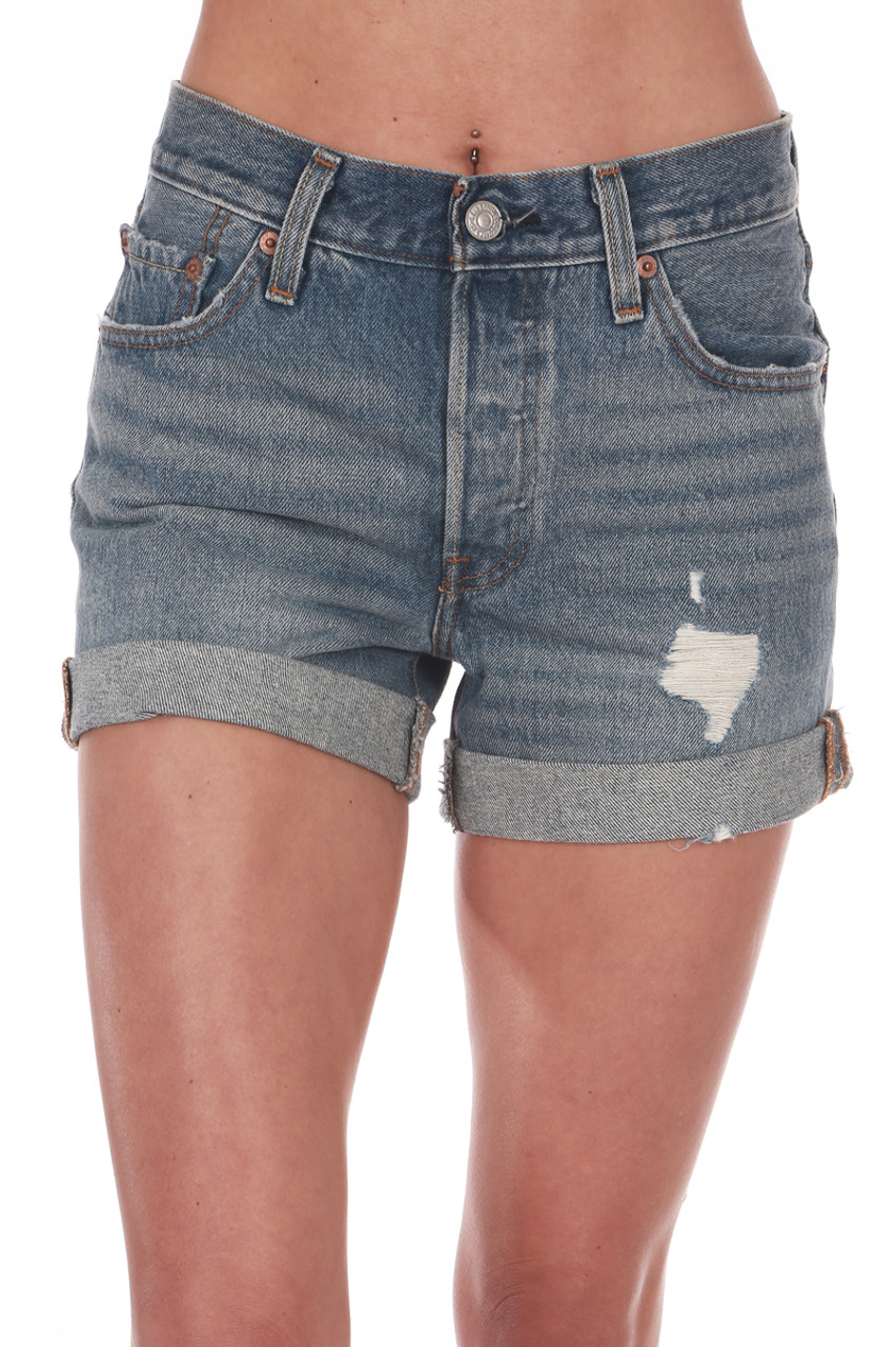 708f8072a9 Front shows cuffed long 501 denim shorts with rip on left side and pockets.