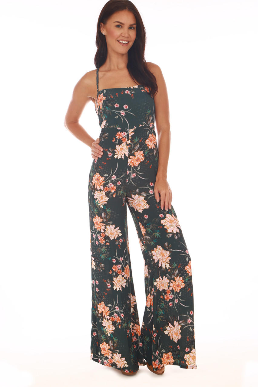 bc29be34065 Front shows dark emerald green jumpsuit all over floral print with  adjustable criss-cross spaghetti