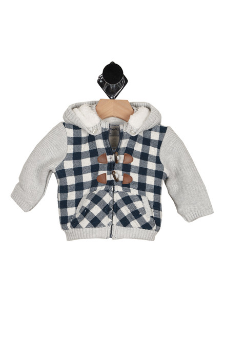 front shows two toned sweater with light grey sleeves and ivory and navy checkered body. Also has button closure at front over zipper