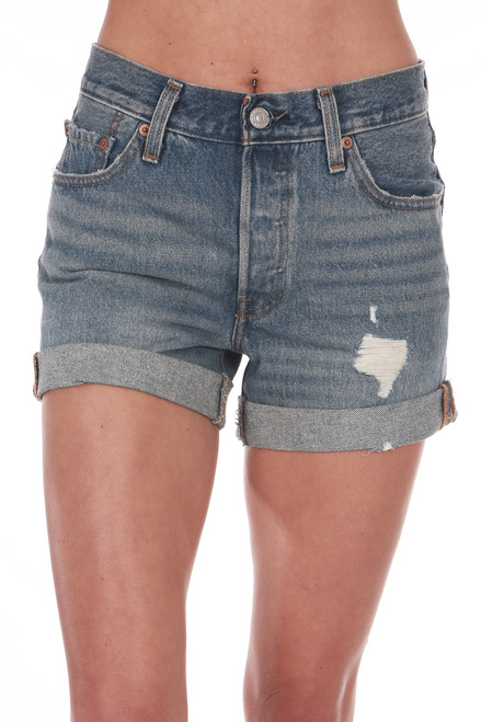 Front shows cuffed long 501 denim shorts with rip on left side and pockets.