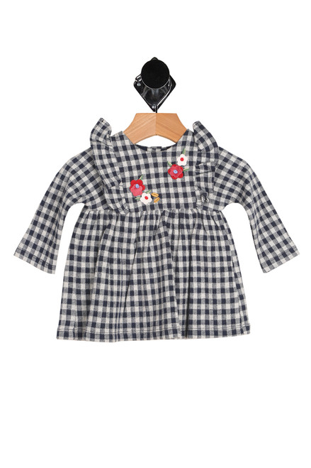 Front shows long sleeve holiday dress  featuring the softest navy & cream plaid material with ruffle detailing at shoulders, flower patches at front and fully lined.