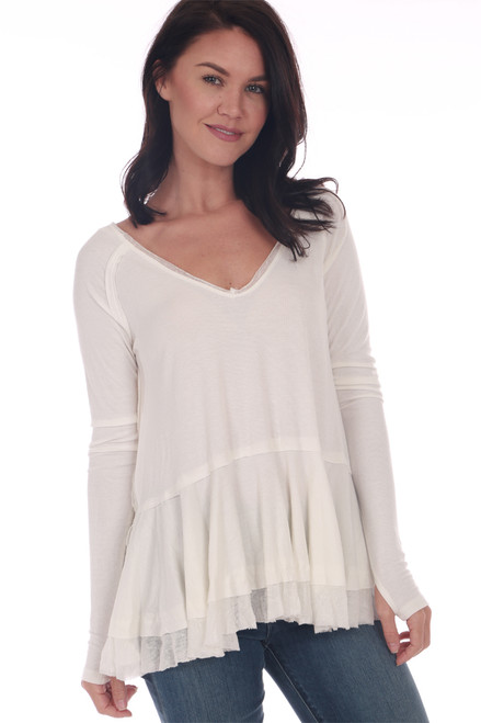Front shows white layered top featuring a v-neck line with long sleeves with thumb holes, tiered ruffle later at bottom and the softest linen blend rib knit material!