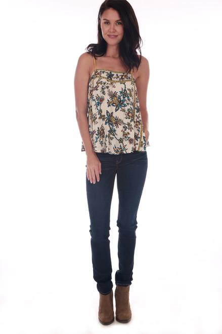 Front shows blue Jeans featuring a mid rise with double button top & zipper fly, soft & stretchy denim material and a skinnier tapered hemline. Shown warn with floral spaghetti strap print tank and brown boots.