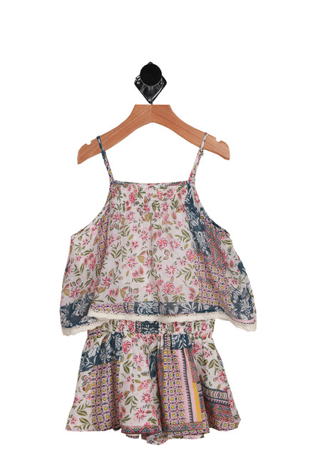 Sydney Romper for Little Kids has small pink flowers on a white background with blue details. This romper features adjustable spaghetti straps with keyhole button at back, elastic waistband and is completely lined. Set is 100% Cotton, Lining is 100% Cotton.  Hand Wash Cold, Air Dry.