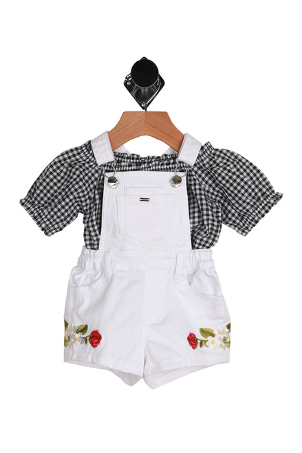 Features white overalls with floral embroidery on sides and elastic waistband.  Black and white gingham top features off the shoulder look with elastic top and bottom hemlines.  Overalls - 98% Cotton, 2% Elastane, Top - 100% Cotton.  Machine Wash Cold, Tumble Dry Low.