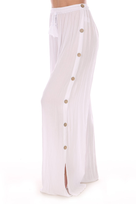 Side view shows the button side.  Wide leg button side pants in sheer white with a high rise fit.  Elastic waist with tie.  Rise is  Approximately 13.5 inches and Inseam is Approximately 28 inches. 100% Rayon.  Machine Wash Cold, Hang Dry.