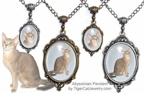 $23.99 Fawn Abyssinian Cat Pendant necklace in Silver or Bronze Gold with a Victorian Style frame has an almost three dimensional look with transparent photo under glass. Two sizes and two colors to choose from with text on back as a free option.#AbyssinianCat#AbyCat#AbyssinianCatJewelry#AbyssinianCatNecklace#VictorianCatJewelry#PetMemorial#TigerCatJewelry
