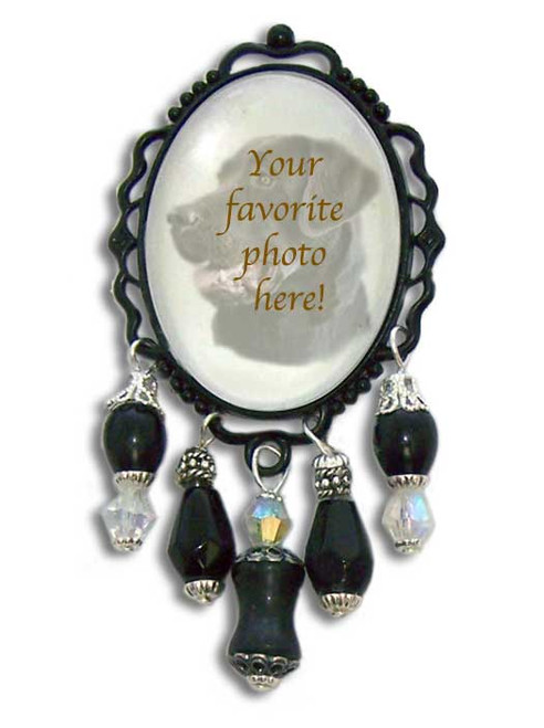 This black framed brooch features a photo of your pet or person under a domed glass cabochon. Crystals and gemstone beads cascade beneath. Makes a very unique gift or special keepsake treasure as a pet memorial or photo tribute pin.