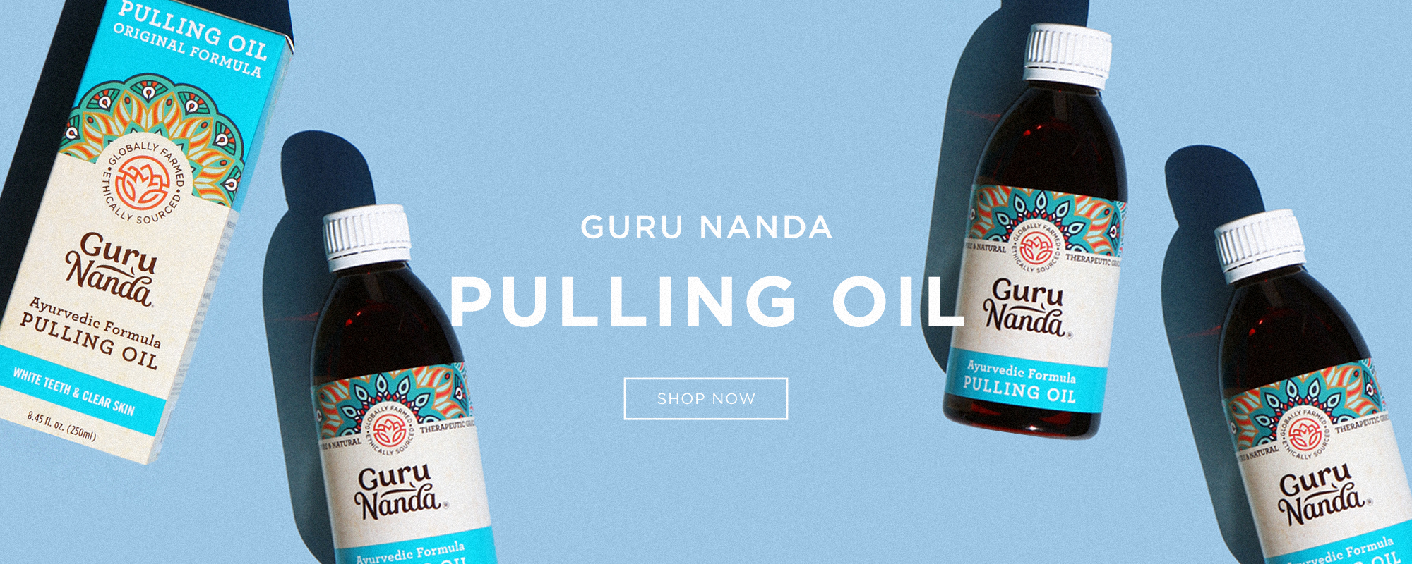 Guru Nanda Pulling Oil - 3 bottles and package laying flat on a blue background. Text reads GURUNANDA PULLING OIL - SHOP NOW