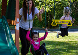 Parents and kids having fun on the Ranger Plus Swing Belts and Trapeze from PlayNation Play Systems.
