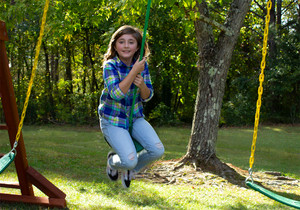 Outdoor view of girl swinging on the Green Disc Swing from PlayNation.