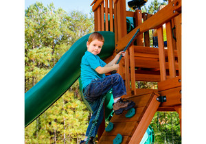 Boy making his way up the Rock Climbing Wall of the Empire Extreme swing set from Playnation