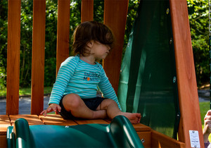 Young child getting ready to slide down the Wave Slide on the Ranger Plus swing set from PlayNation Play Systems.