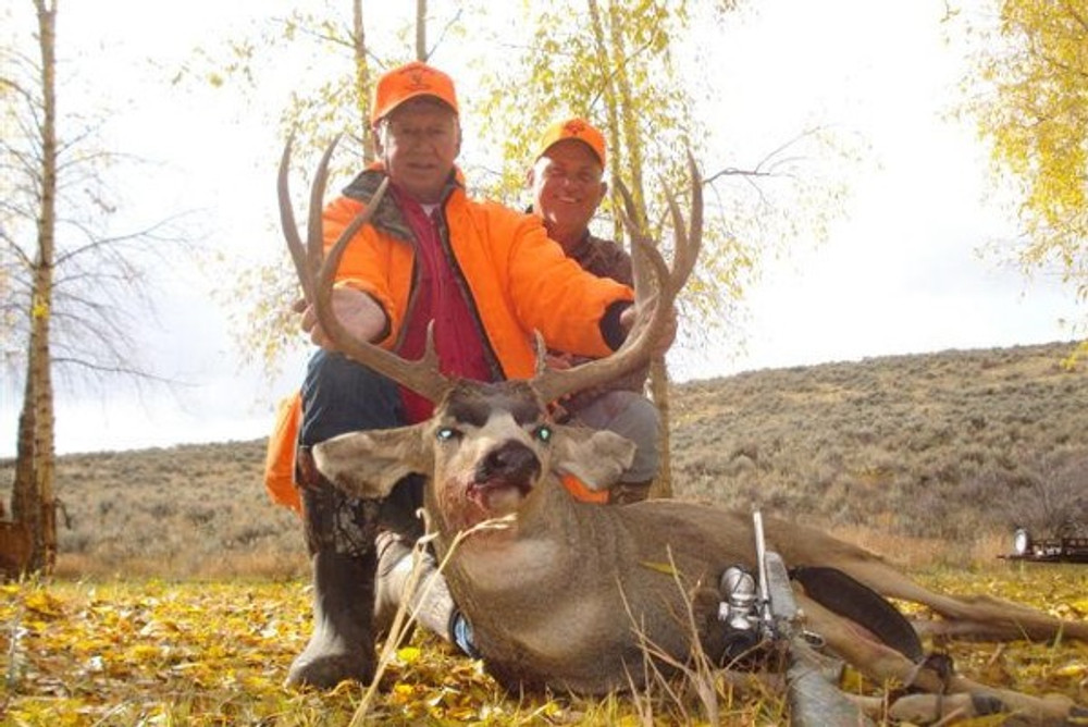 A hunter and his guide with a monster muley.