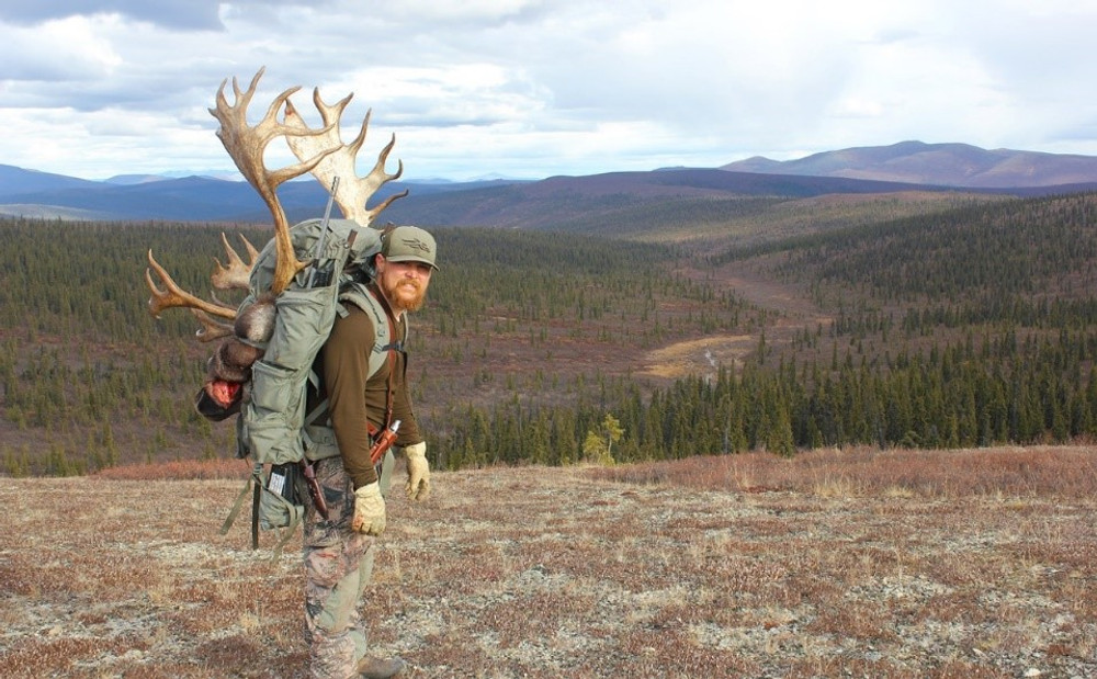 Packing out his trophy caribou.
