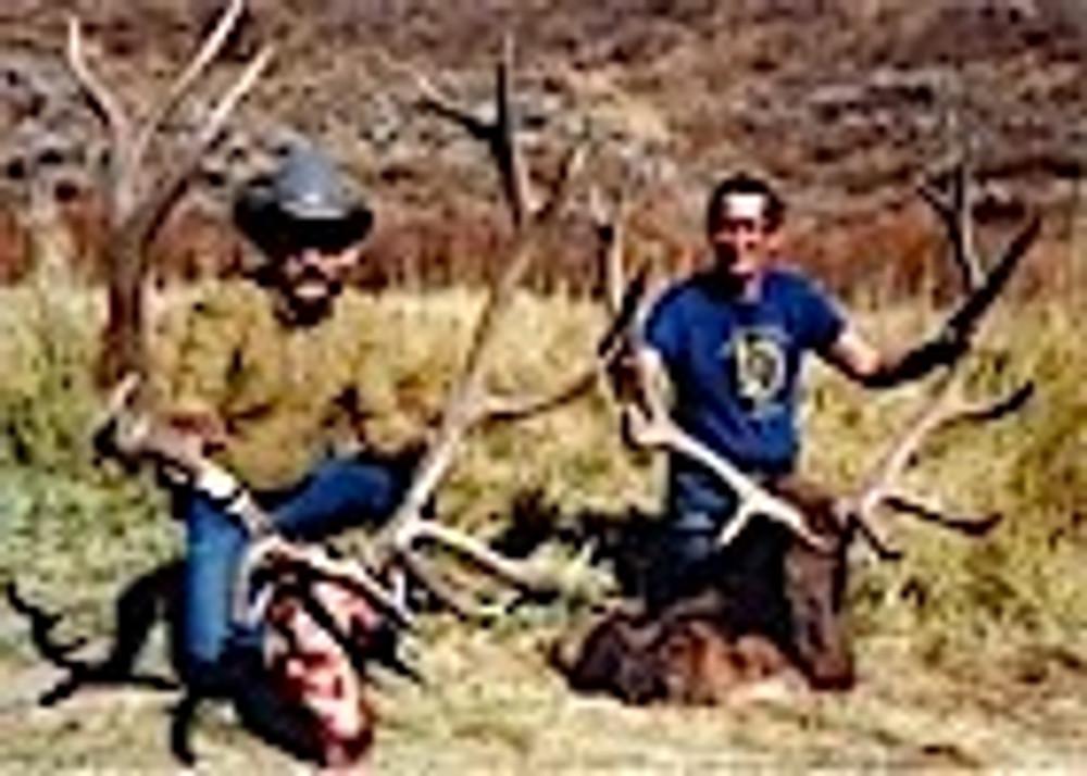 Happy partners with bull elk trophies.