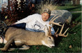 Weird picture of a guy laying next to his trophy whitetail buck.