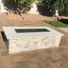 Stainless steel rectangle fire pit cover sitting within the ledge of a fire pit