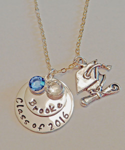 """Hand Stamped Graduation Necklace """"Class of 2016"""" charm, layered Name Charm, and  Cap & Diploma pendant with two Swarovski Crystals in Graduation Colors, all Sterling Silver. It is shown Polished Finish on a Solid Sterling Silver Cable Chain. Choose from five custom finish options. Use the drop down menu if you would like to add Genuine Swarovski Crystal Birthstones.   SIZE:  One Solid Sterling Silver 7/8"""" Round stamped, """"Class of 2016"""" One Solid Sterling Silver 5/8"""" Round Charm with name of choice. Two Swarovski Crystals choice of colors. (Graduation Colors of Blue & White if choice left blank)"""