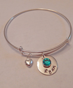"""Hand Stamped Round Name Charm with Genuine Swarovski Birthstone on Expandable Bangle Bracelet all Sterling Silver. One size fits most. It is shown with a Polished Finish. Included is one puffy heart charm , Name Charm and one Genuine Swarovski Birthstone. Choose from five custom finish options. Use the drop down menu if you would like to add more charms or Genuine Swarovski Birthstones.   SIZE:  Expandable one size fits all 2 1/2""""-3"""" Solid Sterling Silver Bangle Bracelet 1.5mm. One Solid Sterling Silver puffy heart charm One Solid Sterling Silver 5/8"""" Round Charm. One Genuine Swarovski Crystal Birthstone choice."""