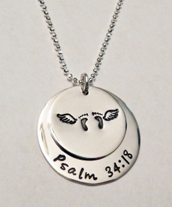 "Stamped Infant Loss Necklace ~ Sterling Silver Child Memorial Necklace ~ ""Psalm 34:18"" Baby Feet & Angel Wings Remembrance Necklace. It is shown with a Polished Finish on a Diamond Cut Bead Chain. Choose from five custom finish options. You can have a Date or Name below the baby feet if you like, or customize the text on the larger piece of silver. Use the drop down menu to add Genuine Swarovski Birthstones.  Psalm 34:18 NIV  The Lord is close to the brokenhearted and saves those who are crushed in spirit.  SIZE: Solid Sterling Silver 1"" Round with ""Always in my heart"" or custom text Solid Sterling Silver 3/4"" Round with baby feet and angel wings (optional name, date, other custom text)"