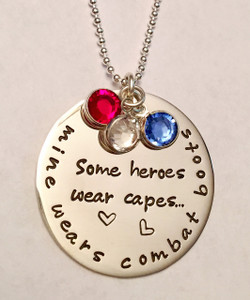 """""""Some heroes wear capes...mine wears combat boots."""" Large Round Stamped Sterling Silver Necklace. Perfect for a Military Wife or Military Mom. Necklace comes with Red, White, and Blue Genuine Swarovski Crystals and is shown with a Polished Finish on a Solid Sterling Silver Ball Chain. Choose from five custom finish options.   SIZE:  Solid Sterling Silver 1 1/4"""" Round 3 Genuine Swarovski Crystals- 1 Red, 1 White, 1 Blue"""