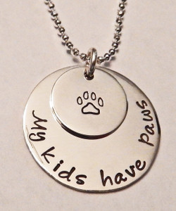 """Hand Stamped .925 Sterling Silver Paw Print Necklace reading, """"My kids have paws."""" Dog Paw/Cat Paw Animal Lover Necklace. Shown with a Polished Finish on a Solid Sterling Silver Diamond Cut Bead Chain. Choose from five custom finish options. Use the drop down menu to add Genuine Swarovski Birthstones.   SIZE:  Solid Sterling Silver 7/8"""" Round reading """"My kids have paws"""" Solid Sterling Silver 1/2"""" Round with Paw Print"""