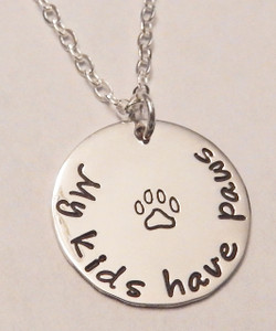 """Hand Stamped .925 Sterling Silver Paw Print Necklace reading, """"My kids have paws."""" Dog Paw/Cat Paw Animal Lover Necklace. Shown with a Polished Finish on a Solid Sterling Silver Cable Chain. Choose from five custom finish options. Use the drop down menu to add Genuine Swarovski Birthstones.  SIZE:  Solid Sterling Silver 3/4"""" Round reading """"My kids have paws"""" with paw print"""