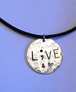 """Semicolon LIVE & Love (Heart Shape) Sterling Silver Round Stamped Recovery or Prevention Necklace and choice of chain. It is shown Hammered on a Black Leather Chain. Choose from five custom finish options. Use the drop down menu to add Genuine Swarovski Birthstones.  This piece is inspired by the Project Semicolon Movement. Project Semicolon (The Semicolon Project) is a faith-based non-profit movement dedicated to presenting hope and love to those who are struggling with depression, suicide, addiction and self-injury. """"A semicolon represents a sentence the author could have ended, but chose not to. The sentence is your life and the author is you."""" - Project Semicolon  SIZE:  Solid Sterling Silver 7/8"""" Round"""