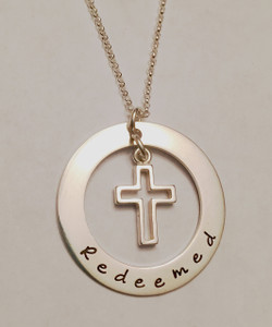 """Redeemed"" Sterling Silver Washer with Floating Cross Necklace, Hand Stamped with choice of chain. It is shown with the word, ""Redeemed,"" however we can customize it to your needs. It is shown with a Polished Finish on a Rolo Chain. Choose from five custom finish options. Use the drop down menu to add Genuine Swarovski Birthstones.  SIZE:  1 1/4"" Solid Sterling Silver Washer hand stamped with ""Redeemed"" Solid Sterling Silver Floating Open Cross"
