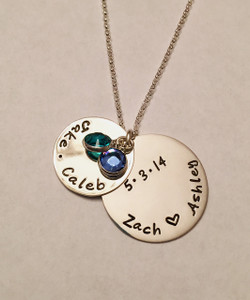 "Hand Stamped Sterling Silver Family Name Necklace with Peek-a-Boo Anniversary Date with Swarovski Birthstone. One Birthstone is included. Shown with a Polished Finish on a Solid Sterling Silver Rolo Chain. Choose from five custom finish options. Use drop down menu to add Genuine Swarovski Birthstones. SIZE: Solid Sterling Silver 1"" Round with names of Dad & Mom with a heart in the middle or custom text Solid Sterling Silver 3/4"" Round with names of children separated by a dot, or custom text One Swarovski Birthstone (Choice of Color)"