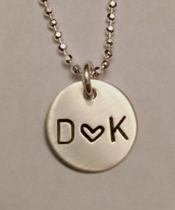 """Initial-Heart-Initial Stamped Circle Charm, all Sterling Silver. It is shown with a Brushed Finish on a Diamond Cut Bead Chain. Choose from five custom finish options. Use the drop down menu to add more stamped charms. Use the drop down menu to add Genuine Swarovski Birthstones.  SIZE:  One Solid Sterling Silver 1/2"""" Round"""
