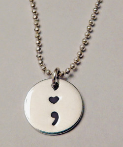 """Semicolon with Heart Dot, all Sterling Silver, Small, Round Hand Stamped Necklace and choice of chain. ~ Project Semicolon ~ Depression, Suicide, Addiction & Self-Injury Recovery & Prevention. Choose from five custom finish options. It is shown with a Polished Finish on a Solid Sterling Silver Diamond Bead Chain. Use the drop down menu to add Genuine Swarovski Birthstones.   This piece is inspired by the Project Semicolon Movement. Project Semicolon (The Semicolon Project) is a faith-based non-profit movement dedicated to presenting hope and love to those who are struggling with depression, suicide, addiction and self-injury. """"A semicolon represents a sentence the author could have ended, but chose not to. The sentence is your life and the author is you."""" - Project Semicolon   SIZE:  Solid Sterling Silver 1/2"""" Round"""