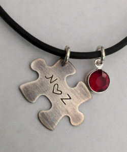"Jigsaw Puzzle Piece Stamped Initial-Heart-Initial, all Sterling Silver Autism Awareness with Genuine Swarovski Birthstone and choice of chain. It is shown with an Aged Finish on a Black Leather Chain with Solid Sterling Silver Findings. Choose from five custom finish options.The Swarovski Crystal can be blue for autism awareness if you like. Use the drop down menu to add Genuine Swarovski Birthstones.   SIZE: Solid Sterling Silver 24 gauge Jigsaw Puzzle Piece approx. 4/5"" x 1/2"" One Genuine Swarovski Crystal Birthstone choice"