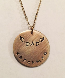 "Superman Dad Memorial Necklace for son or daughter in Sterling Silver, Hand Stamped. ""DAD"" can be surrounded with hearts instead of angel wings if a memorial piece is not needed. It is shown with an Aged Finish on a Solid Sterling Silver Cable Chain. This handmade necklace is Hand Stamped with, ""DAD"" surrounded with angel wings stamped in the center and ""superman"" stamped around the bottom. Choose from five custom finish options. Use the drop down menu to add Genuine Swarovski Birthstones. Optional upgrade to thicker Sterling Silver (from 20 gauge to 16 gauge) that can have text stamped on the back.   SIZE: 1"" Round (Optional upgrade from 20 gauge thickness to 16 gauge)"