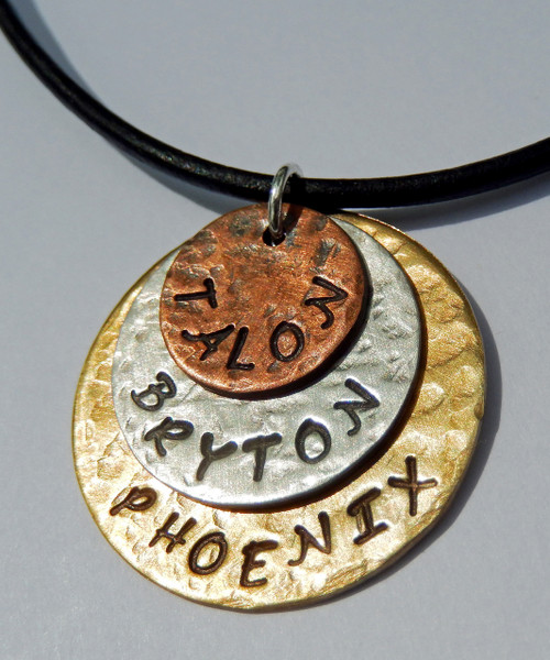 """Personalized, Hand Stamped, Triple Stacked Mixed Metal Necklace with 3 names on Solid Brass, Solid Sterling Silver, and Solid Copper ~ Mommy or Daddy Unisex Necklace with choice of chain. It is shown with an Oxidized Hammered Finish on a Black Leather Chain with Solid Sterling Silver Findings. Choose from five custom finish options. Use the drop down menu if you would like to add Genuine Swarovski Birthstones..    SIZE: Solid Brass 1"""" Round  Solid Sterling Silver 3/4"""" Round  Solid Copper 1/2"""" Round"""
