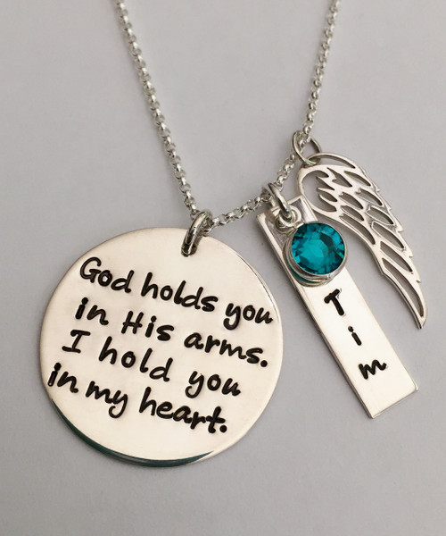 "Stamped ""God holds you in His arms, I hold you in my heart"" with Rectangle NameTag, Angel Wing, and Genuine Swarovski Birthstone Necklace, all Sterling Silver with choice of chain. Choose from five custom finish options. Use the drop down menu to add Solid Sterling Silver Stamped Rectangle Tags. Use the drop down menu to add Genuine Swarovski Birthstones. *STERLING SILVER SPACERS UPON REQUEST ONLY (Not available on large chains)  SIZE: Solid Sterling Silver 1"" Round Solid Sterling Silver 20 gauge Rectangle Name Tag approx. 1"" x 1/4"" (may vary slightly depending on length of name) Solid Sterling Silver Angel Wing One Genuine Swarovski Crystal Birthstone choice *Sterling Silver Spacers upon request only (Not available on large chains)"