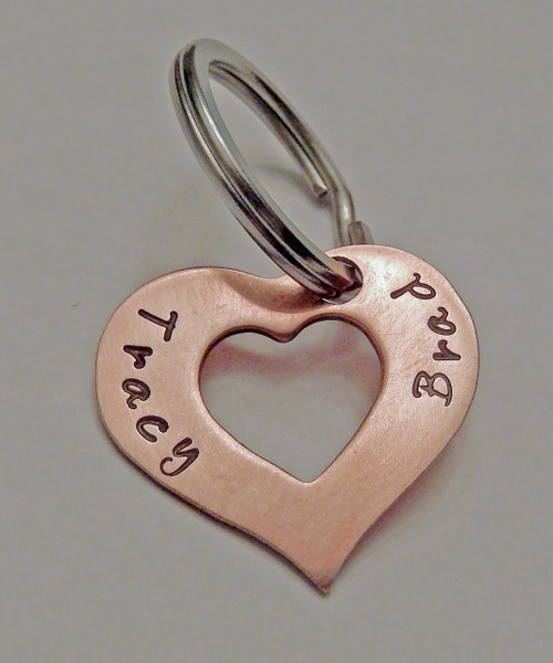 "Solid Copper Heart Washer Keychain with names Custom Hand Stamped. It is shown with a Brushed Finish. Choose from five custom finishes. Optional Black Leather Case.   SIZE: Solid Copper 1"" x 1/2"" Heart Washer"