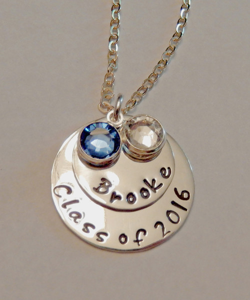 """Hand Stamped Graduation Necklace """"Class of 2016"""" charm and layered Name Charm with two Swarovski Crystals in Graduation Colors, all Sterling Silver and choice of chain. It is shown Polished Finish on a Solid Sterling Silver Cable Chain. Choose from five custom finish options. Use the drop down menu if you would like to add crystals.   SIZE:  One Solid Sterling Silver 7/8"""" Round stamped, """"Class of 2015."""" One Solid Sterling Silver 5/8"""" Round Charm with name of choice. Two Swarovski Crystals choice of colors. (Graduation Colors of Blue & White if choice left blank)"""